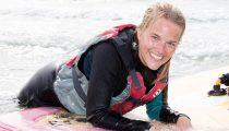 Pige på surfbraet i vandet